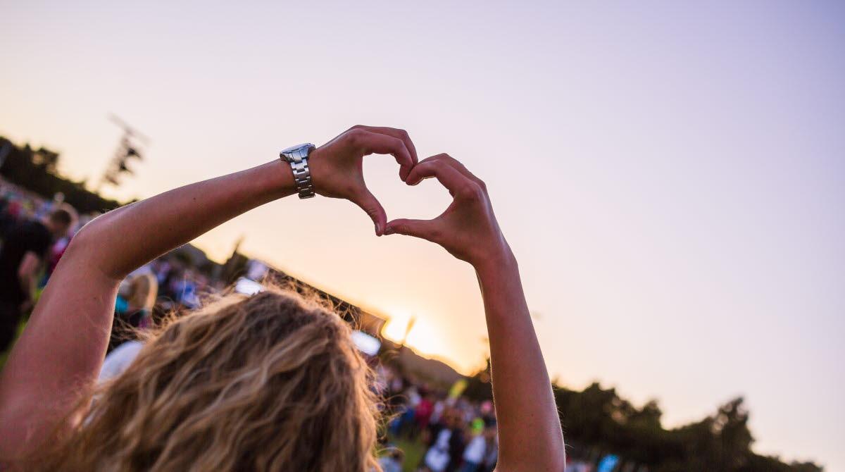 En kvinnlig åskådare på en konsert sträcker upp sina armar i luften och bildar ett hjärta med sina händer.