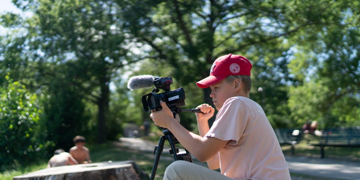 En kille i röd keps och ljus t-shirt sitter och filmar naturen runt omkring honom.