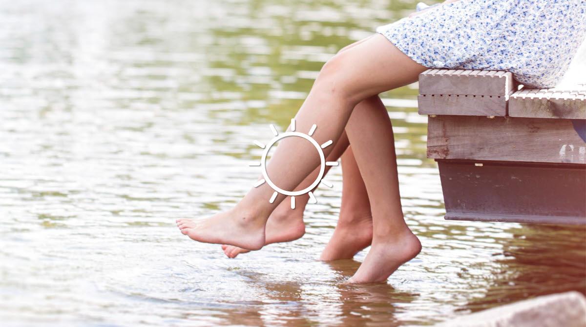 Två personer sitter på en brygga och doppar sina fötter i vattnet.