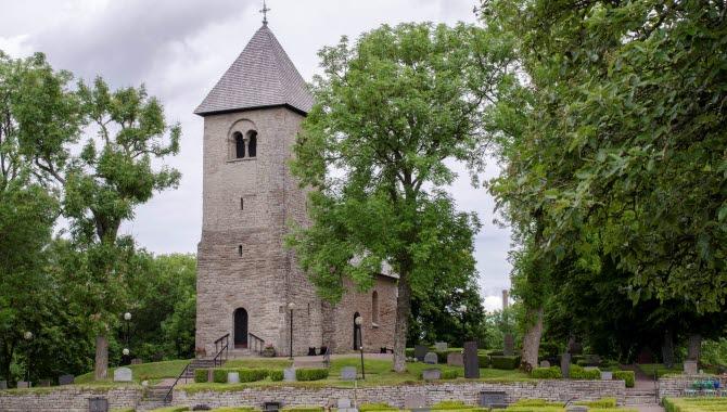 En liten medeltida stenkyrka. I förgrunden syns en kyrkogård med en låg stenmur. Gröna träd kantar bilden.