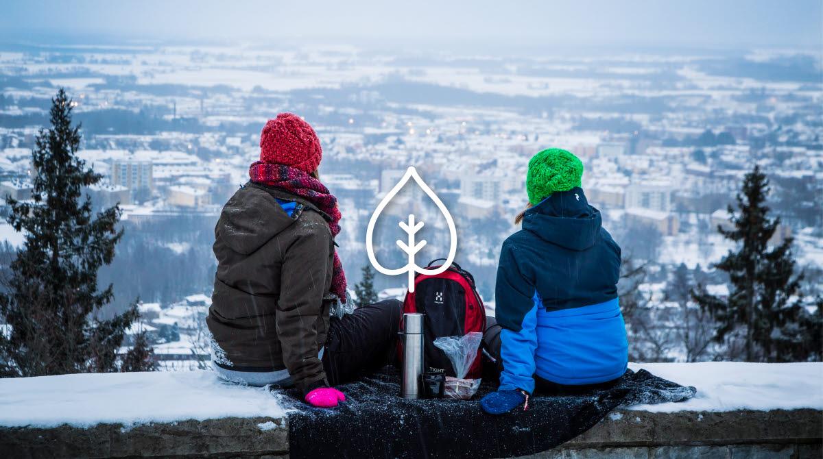 Två personer i röd och grön mössa sitter på kanten av en mur och blickar ut över utsikten. Mellan sig har de fika med en termos varm dryck.