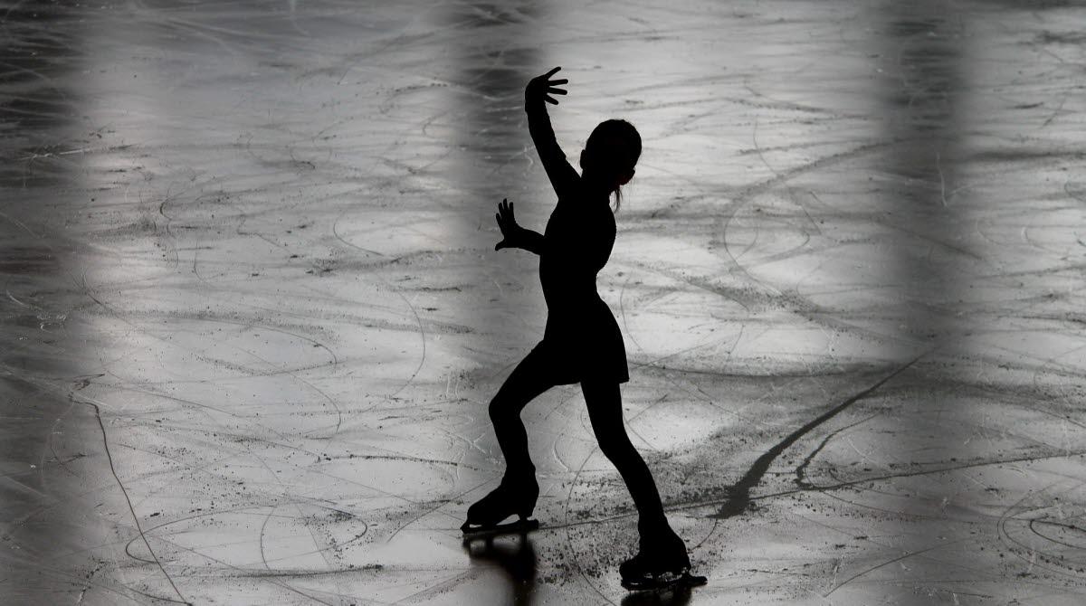 En mörk siluett åker konståkning över isen