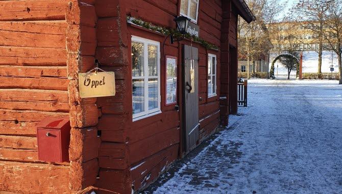 """Fasaden på en röd timmerstuga. På knuten hänger en träskylt med texten """"Öppet""""."""