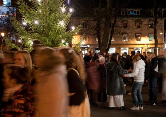Luciafirande i stadsparken. Många människor är i rörelse och julgranen är tänd.