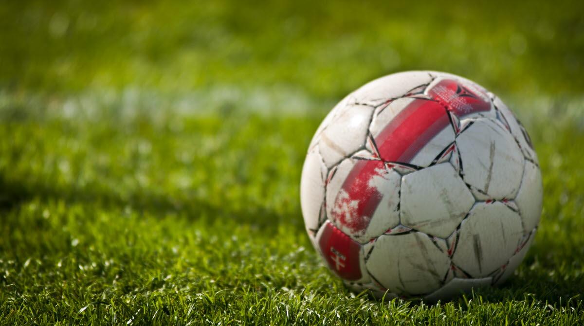 Röd och vit fotboll ligger i det gröna gräset på fotbollsplanen.