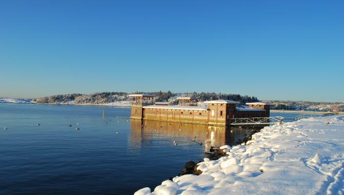 Strömstads kallbadhus en solig och klar vinterdag. Snö ligger på marken,