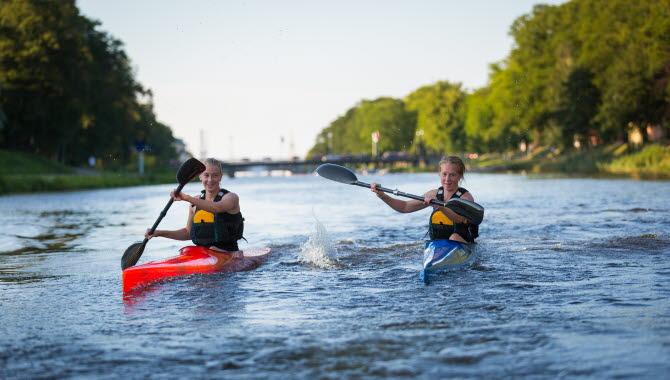 En sommardag där två ungdomar är ute och paddlar kajak i Lidan i Lidköping.
