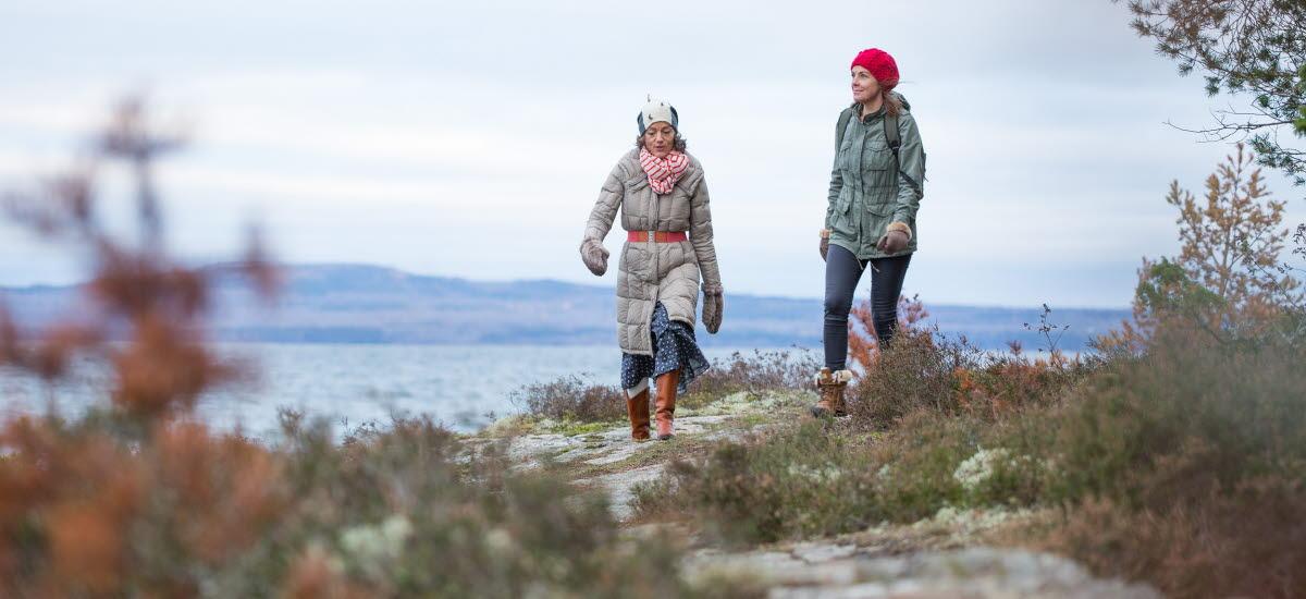 Två kvinnor vandrar i naturen på vintern. Berget Kinnekulle och sjön Vänern syns bakom dem.