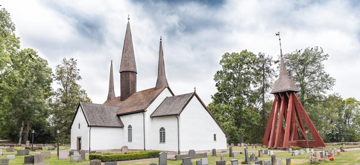 Vy över Kungslena kyrka med en klockstapel intill utanför Tidaholm en sommardag.