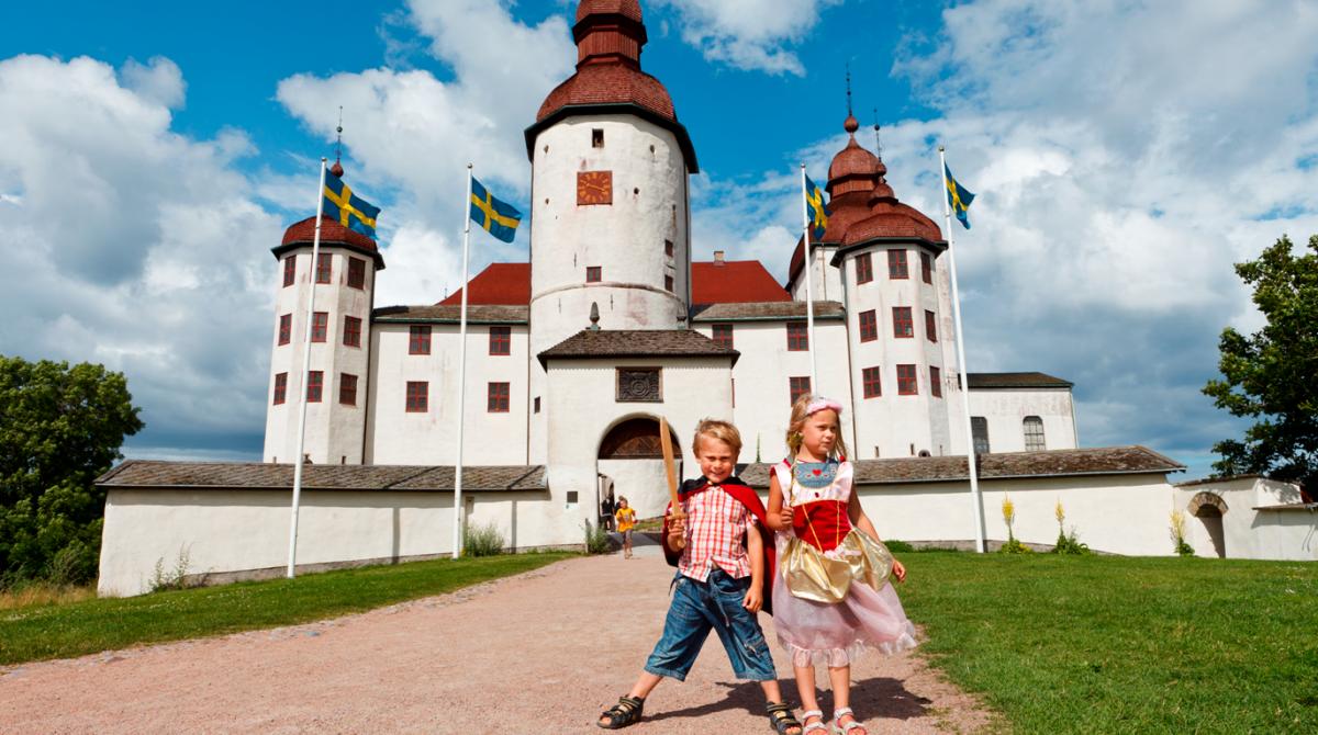 Två barn framför ett vitt slott.