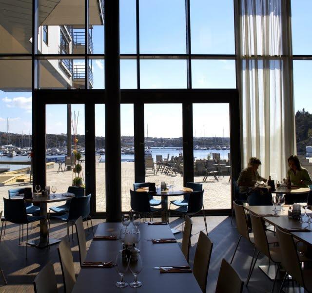 Lounge med sittplatser och höga panoramafönster på Strömstad Spa hotell.