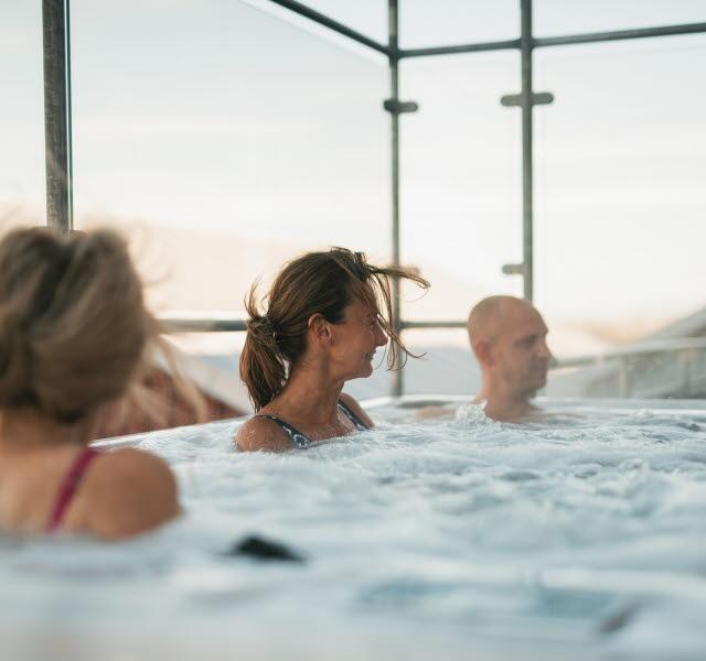 Tre personer sitter och njuter i badtunna i skärgården Havskattens konferens