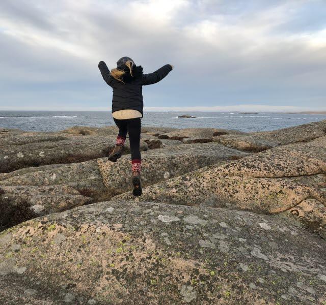 Flicka som hoppar fram på klippor