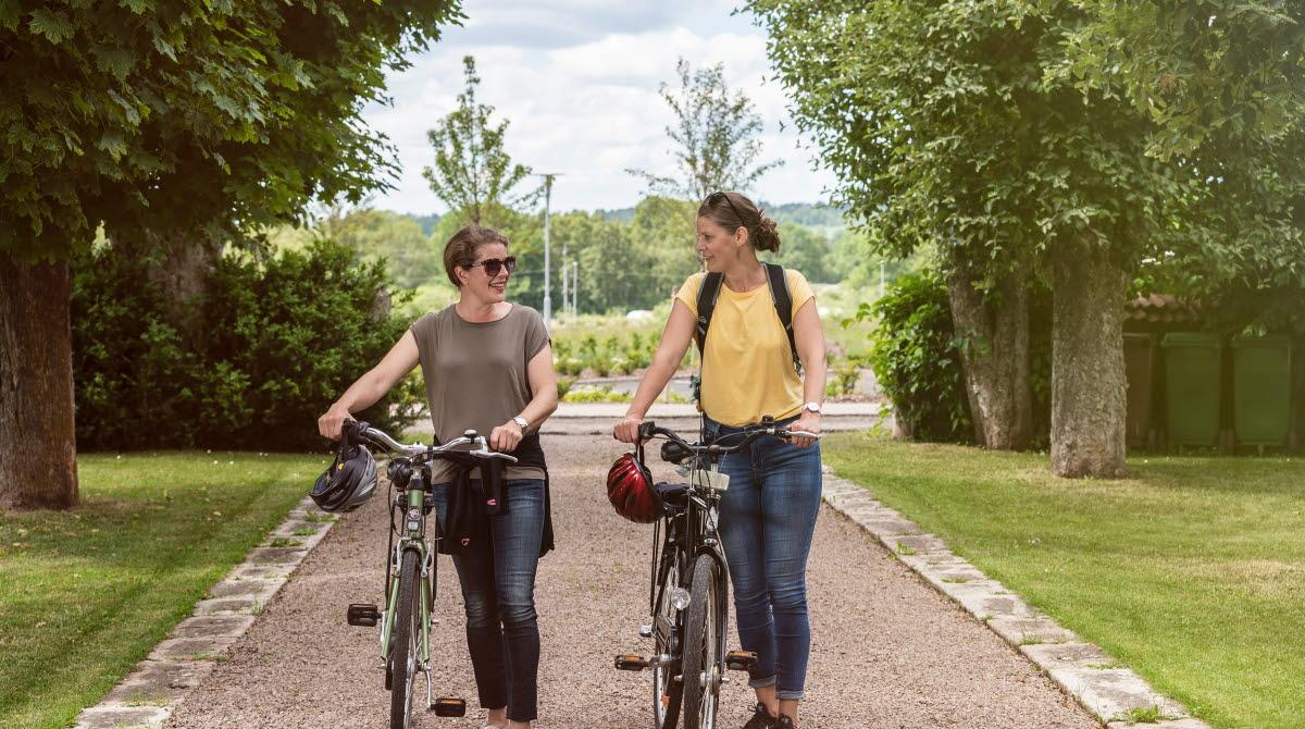 Två kvinnor som leder var sin cykel uppför en grusgång.