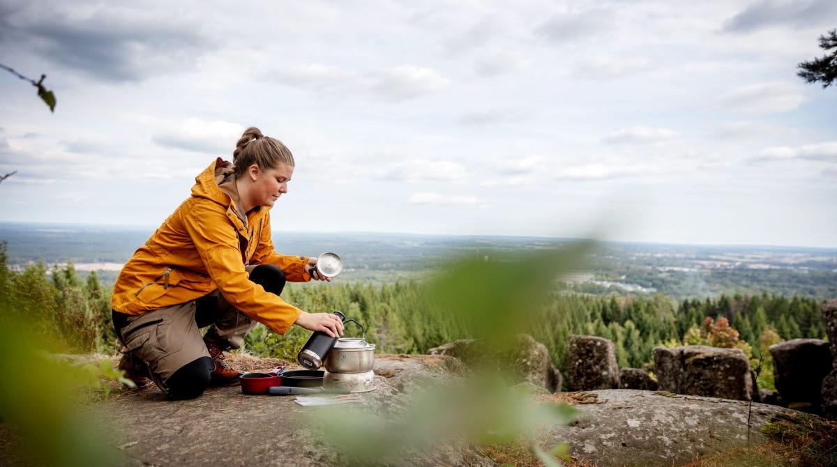 Tjej i gul jacka sitter på kanten av ett berg och förbereder mat i trangiakök. Utsikten i bakgrunden är magisk.