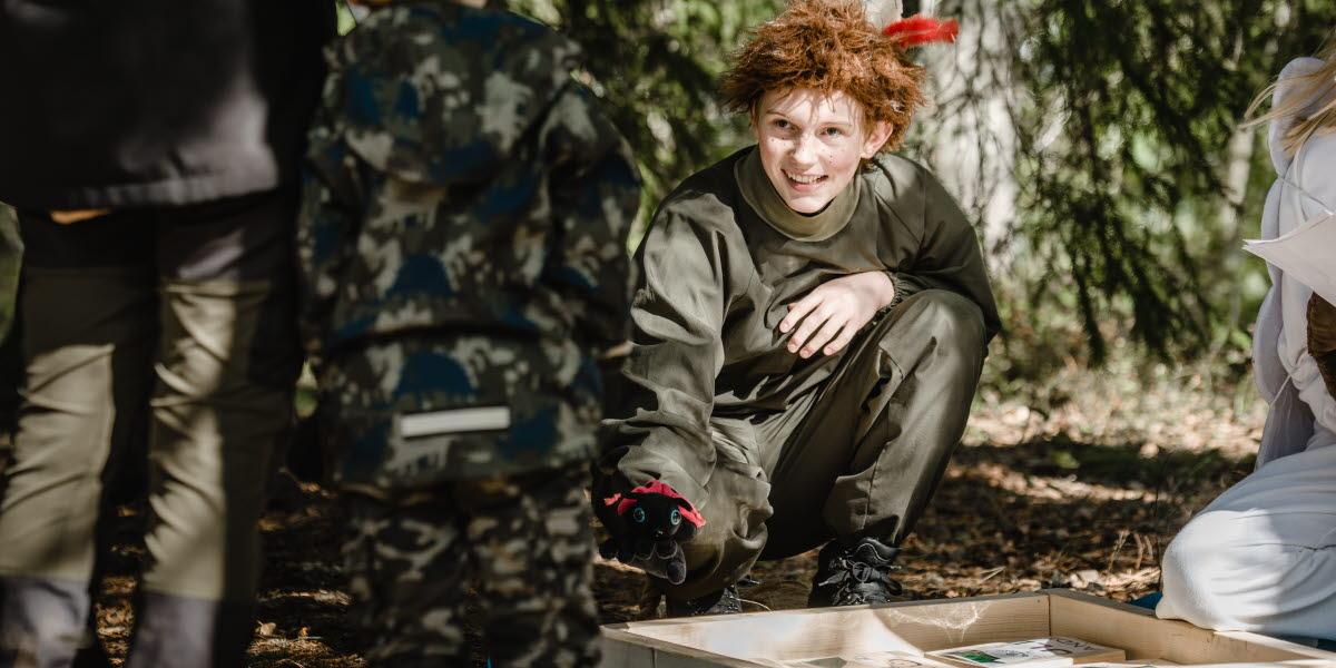 Skogsmulle med en röd fjäder som sticker upp ur det rufsiga håret. Möter liten nyfiken pojke.