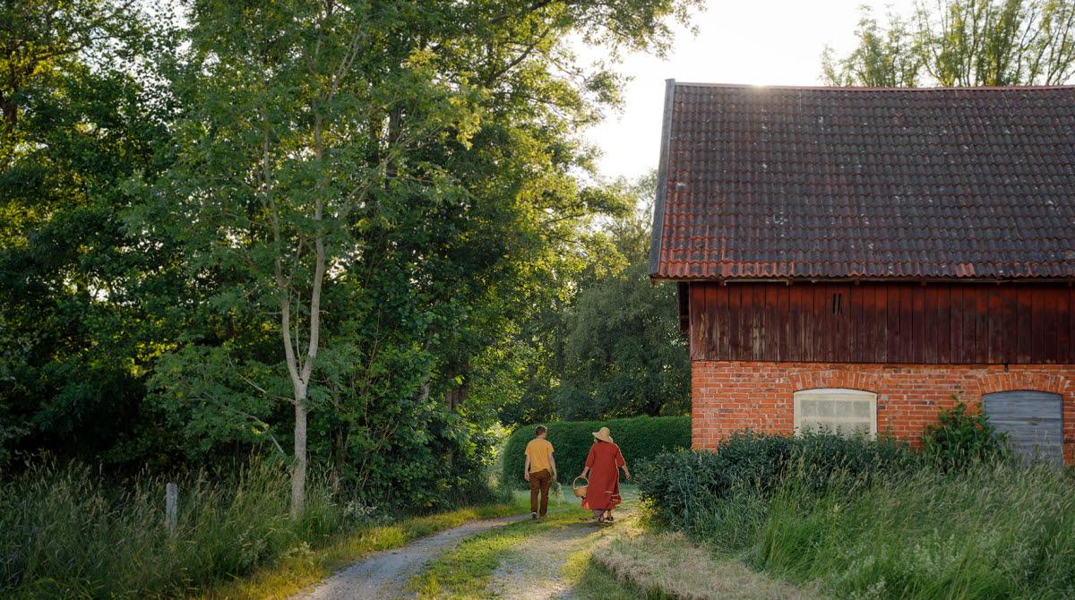 Två personer som går på en grusväg. Gröna träd runtomkring. En röd ladugård vid sidan.