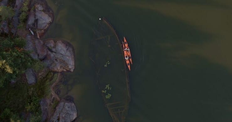 En flygbild där man ser ett vrak i en sjö och en kajak som ligger bredvid