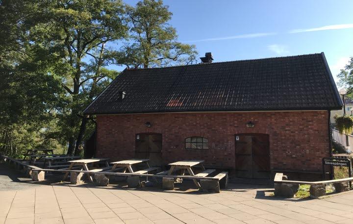 Röd tegelbyggnad med bänkar och bord framför.