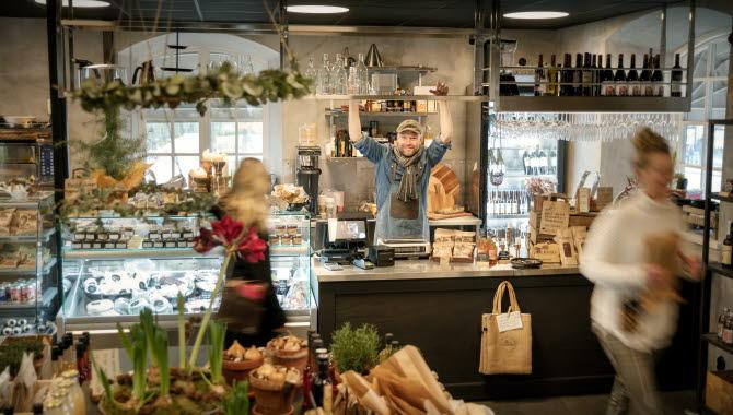 Bild på insidan av en butik. I förgrunden syns blommor och lokala matprodukter. Längst bak i rummet står en man som sträcker armarna över huvudet.