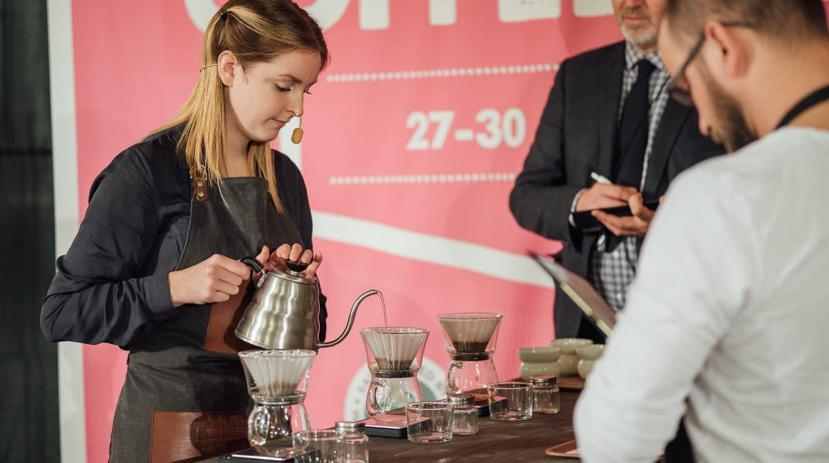 En kvinna brygger kaffe på en scen med domare som tittar på