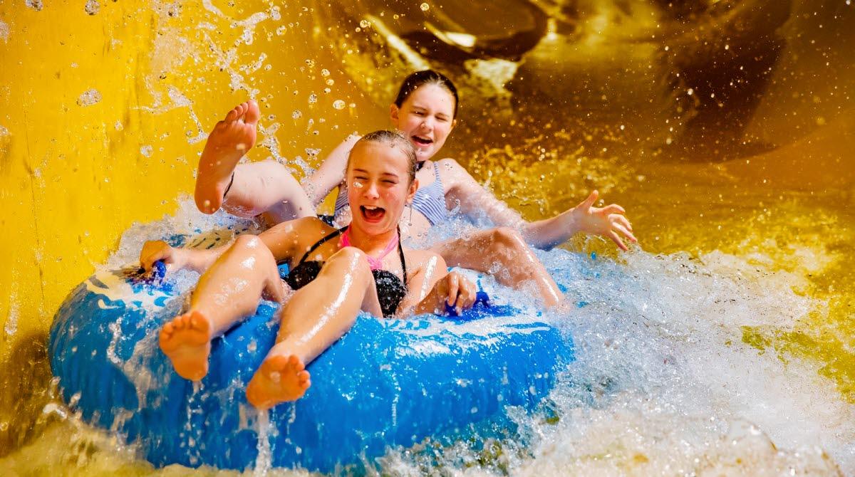 Två superglada tjejer åker på en blå badring i en gul vattenrutschkana så att vattnet stänker.