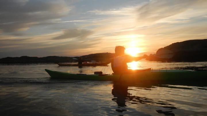 Två personer paddlar i vacker solnedgång.