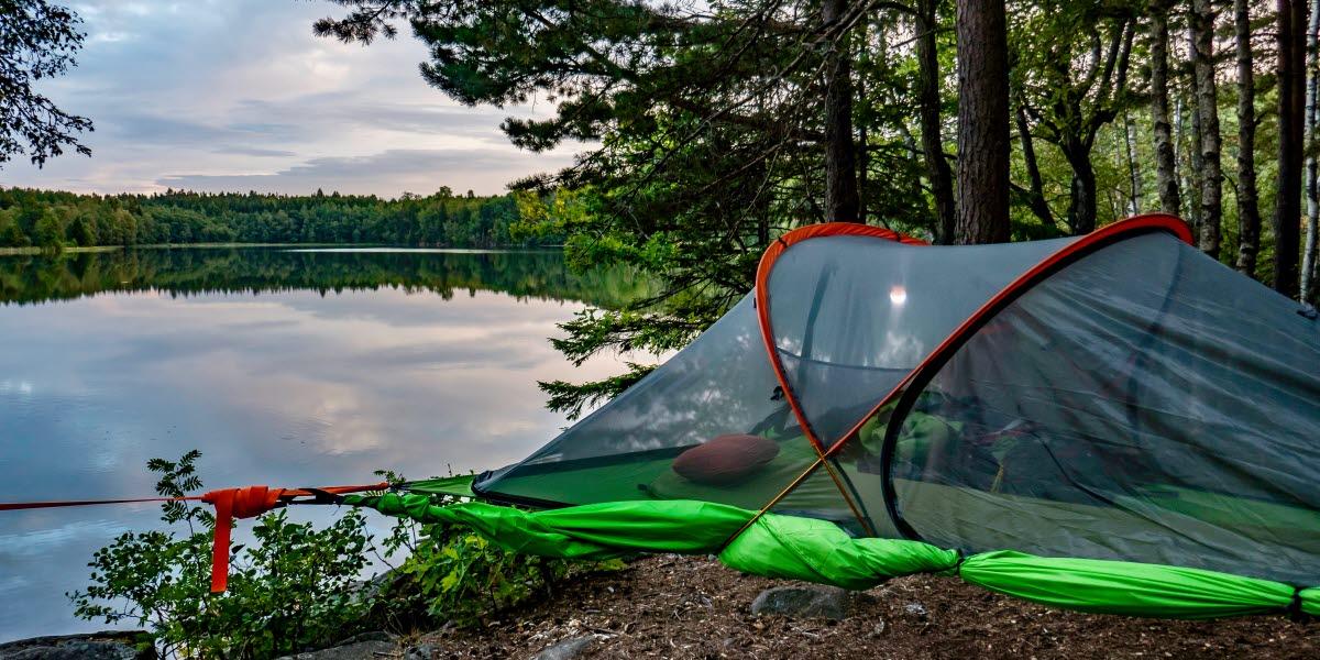 Ett tält uppspänt i träden intill en spegelblank sjö