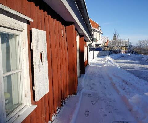 """Röd stuga """"Stötatomten"""" i Gamla stan i Mariestad, vintertid med snö."""
