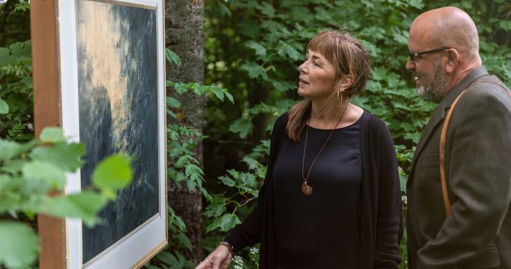 Man och kvinna som står och kikar på en tavla bland träden.