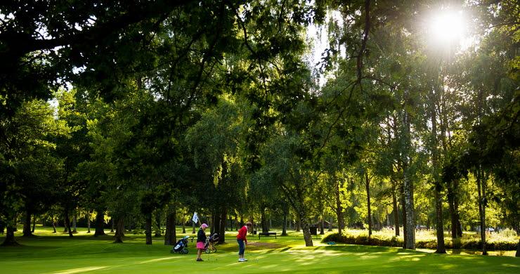 Två kvinnor står och golvar i en grönskande omgivning med solen som skiner igenom mellan träden.