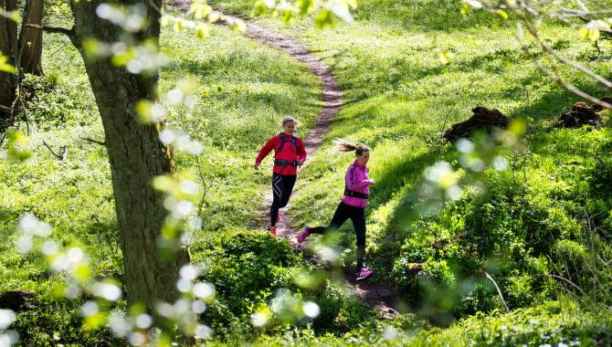 Två kvinnor springer på en stig genom lövskogen.