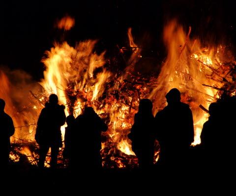 Brinnande brasa med människor som står och tittar på elden en natt.
