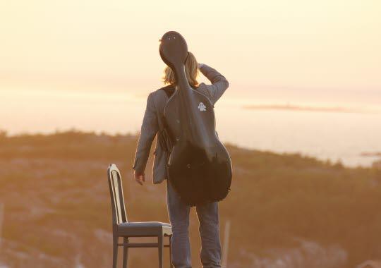 Solnedgång och en musiker står uppe på Valfjäll, Sydkoster under Kosterhavsfestivalen.