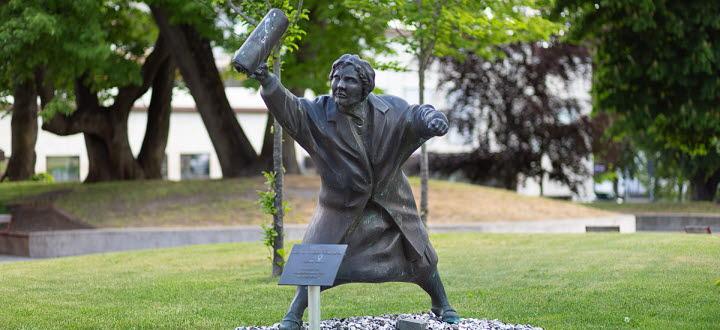 Staty på dam med handväska i luften