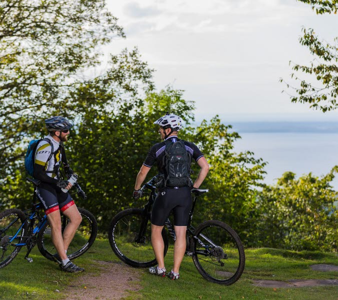 Mountainbike-cyklister som vilar vid en vacker utsikt mot vatten