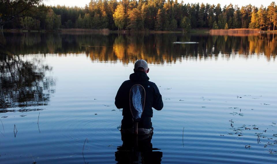 En man som står och fiskar vid en sjö på hösten.
