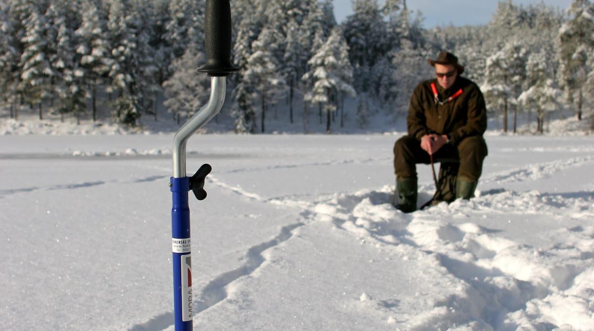 En isborr på en snöig sjö med en man sittandes på en pall bakom.