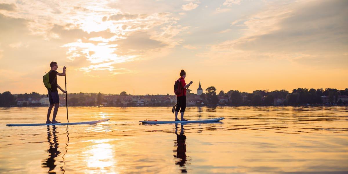 Två personer paddlar stand up paddling över en stilla Vättern i kvällssolen.