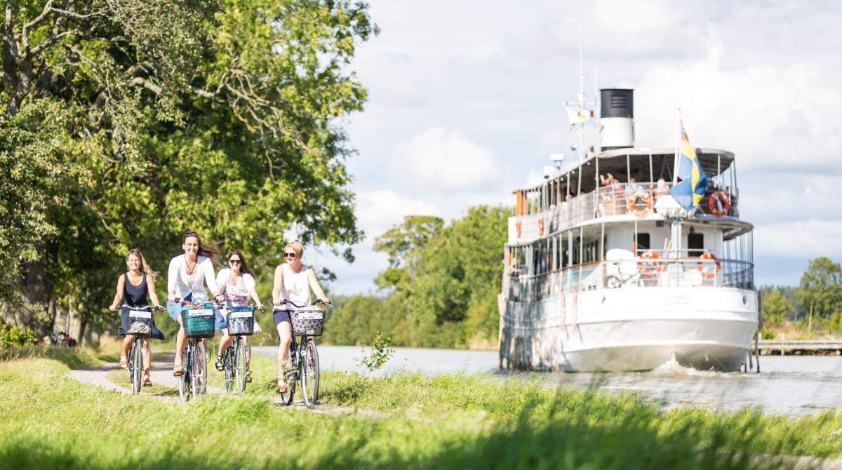 Fyra kvinnor cyklar i de gröna lummiga omgivningarna längs Göta Kanal. Bredvid dem i kanalen kör en passagerarångbåt.