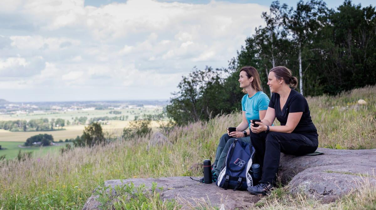 Två kvinnor som sitter på en sten och fikar och tittar på utsikten.