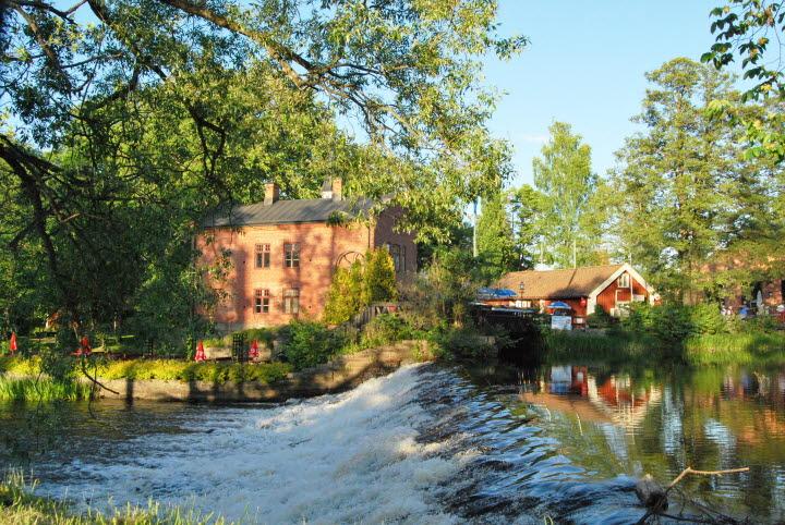 Bild på Turbinhuset som är Tidaholms konsthall och Kaffestugan med ett litet vattenfall framför i sommargrönska.