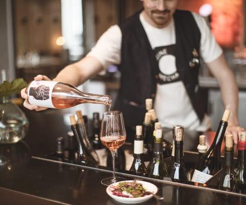 Man häller upp ett glas vin i en bar