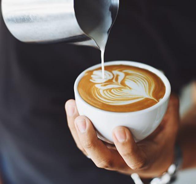 En person häller upp skummad mjölk i en kopp latte och formar mönstret av en tulpan
