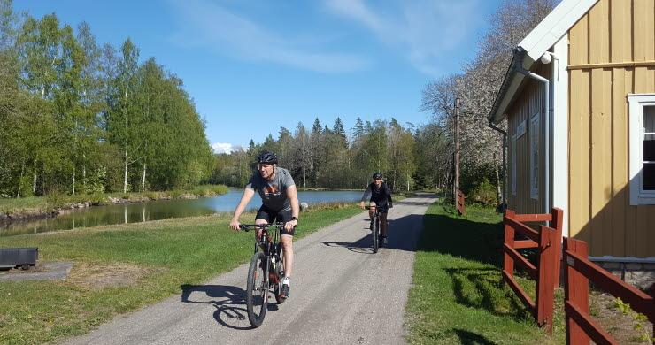 Två personer cyklar längs Göta kanal nära Sjötorp.