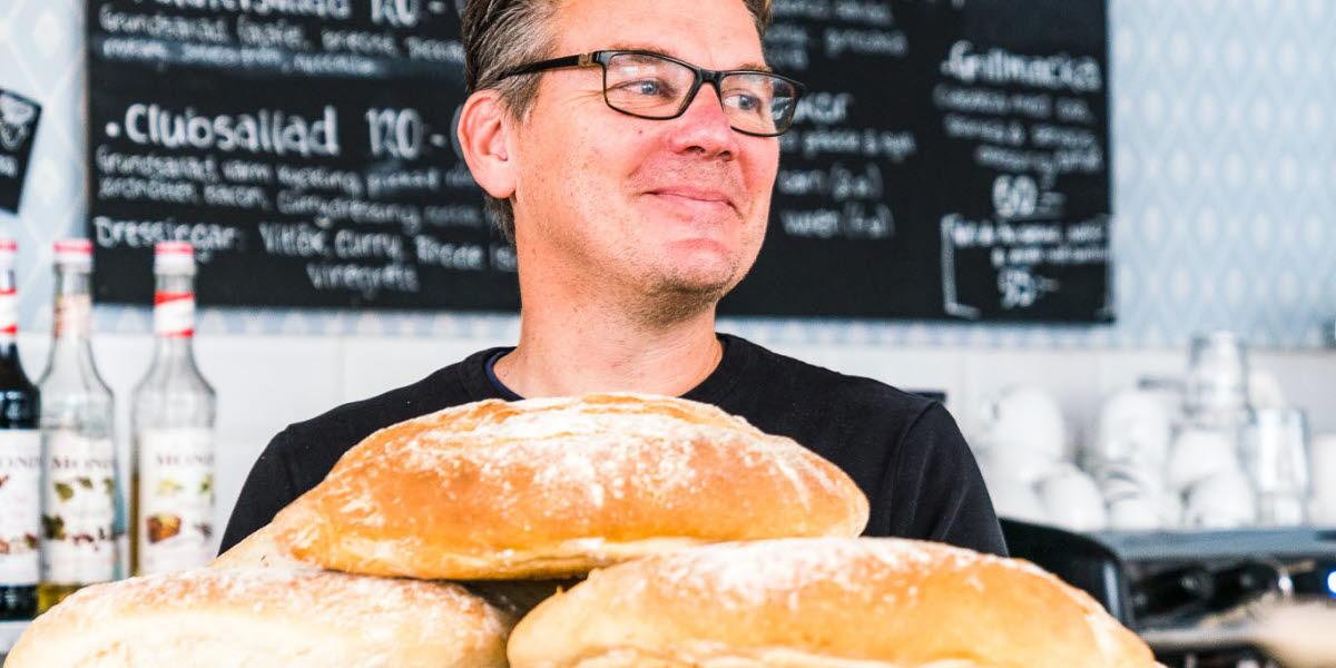 Kaféägare i Hjo med nybakat bröd inne på sitt café Vete & Råg.
