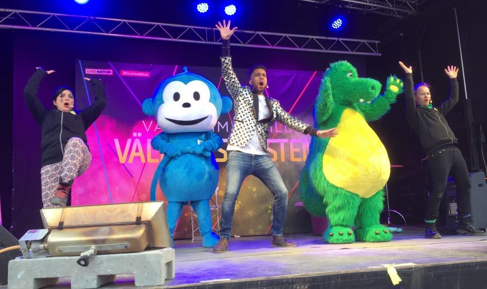 Figurer från barnprogram i Tv står på en scen tillsammans med tre vuxna som dansar.