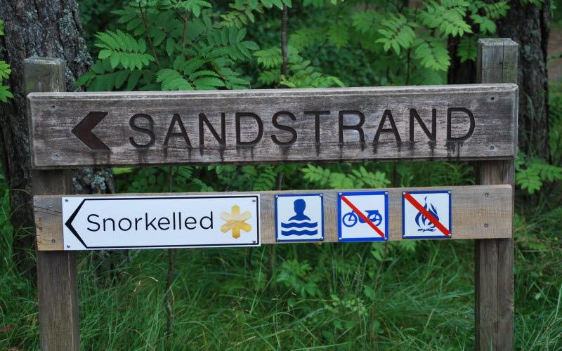 Träskylt som visar vägen till strand med snorkelled på ön Saltö