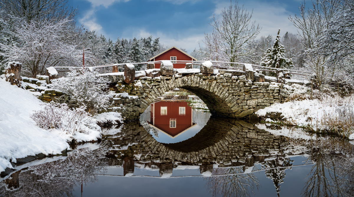 An old stone bridge with a red house behind and snow on the ground