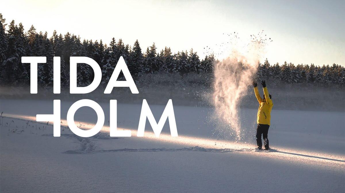 En man som står i snön och kastar upp snö